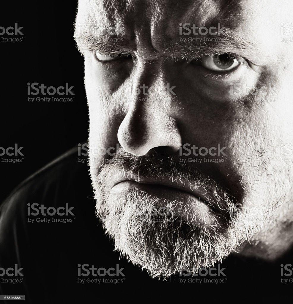 Threatening, angry mature man glowers in black and white stock photo