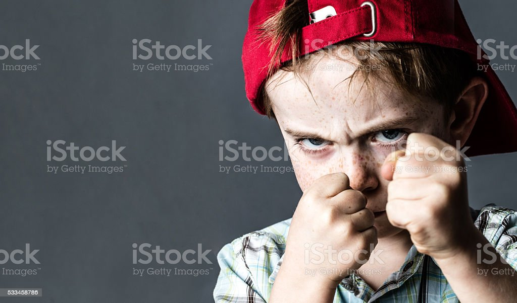threatening boy with freckles and red hat back looking violent stock photo