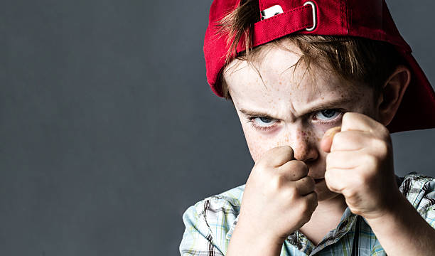 threatening boy with freckles and red hat back looking violent threatening 6-year old boy with freckles and a red hat back looking violent with fists in the forefront,acting like a little bully at school, contrast effects over grey background studio aggressively stock pictures, royalty-free photos & images