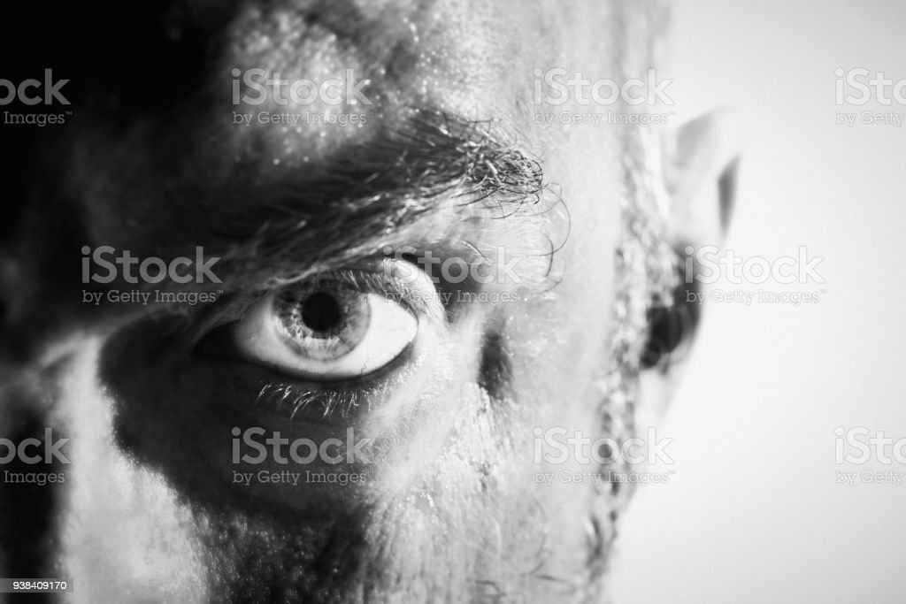 Threatening man glaring angrily in black-and-white close-up stock photo