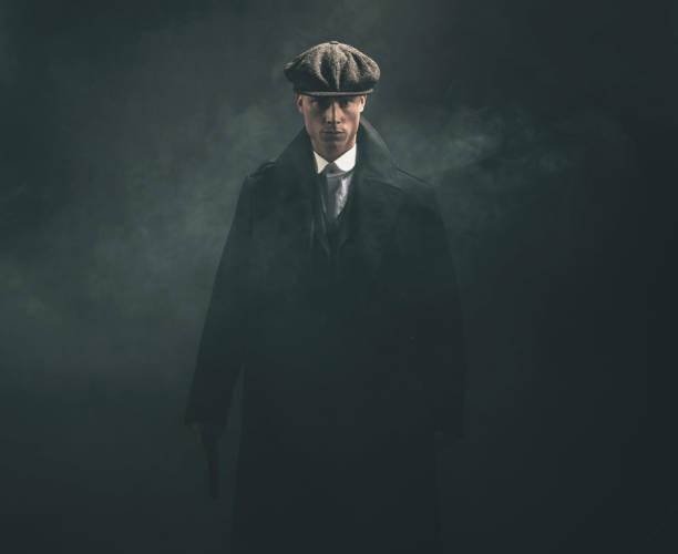 threatening retro 1920s english gangster holding gun in smoky room. - gangster zdjęcia i obrazy z banku zdjęć