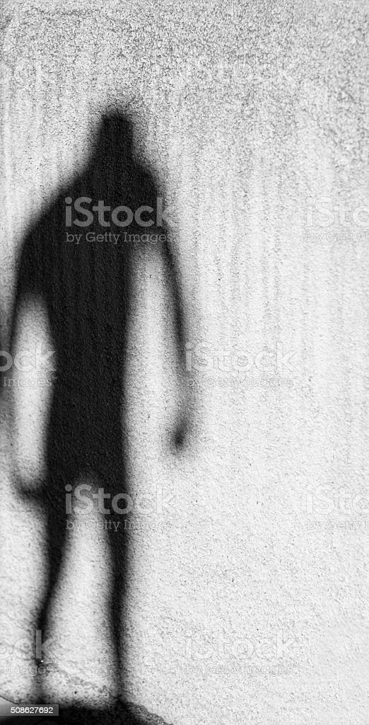 Threatening Silhouette on Old White Wall stock photo