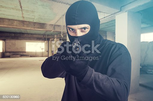 istock Threatening situation concept. Masked criminal pointing a gun 520130960