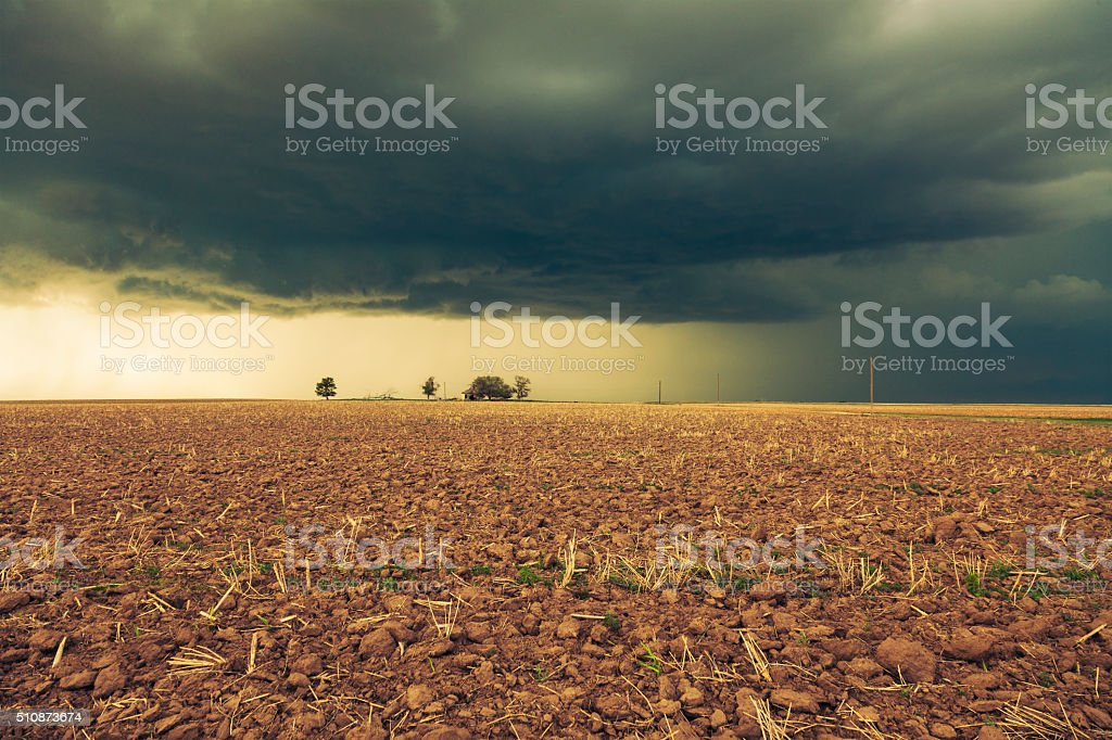 Threatening storm clouds gather over dry farm land stock photo