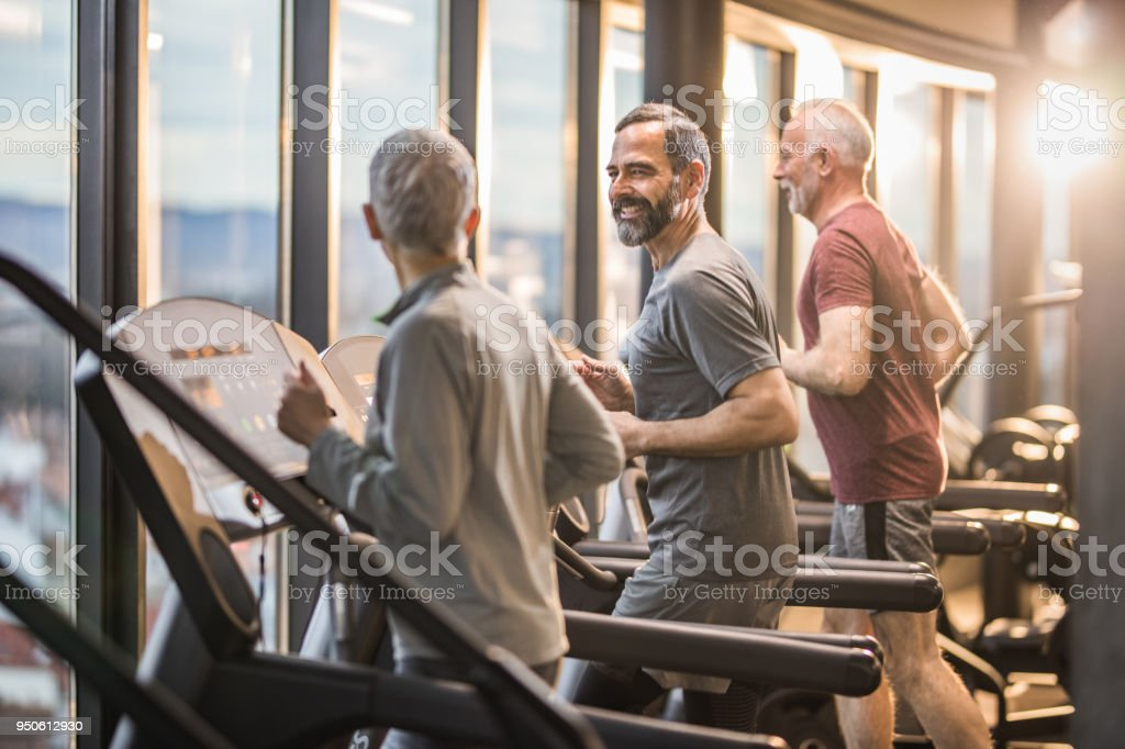 Three active seniors exercising on treadmills in a health club and communicating. stock photo