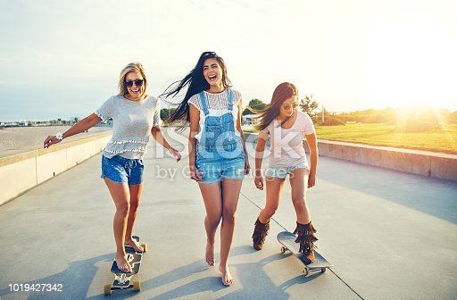 Three active pretty young woman on a day at the seaside enjoying their summer vacation skateboarding along a beachfront promenade at sunrise laughing and smiling