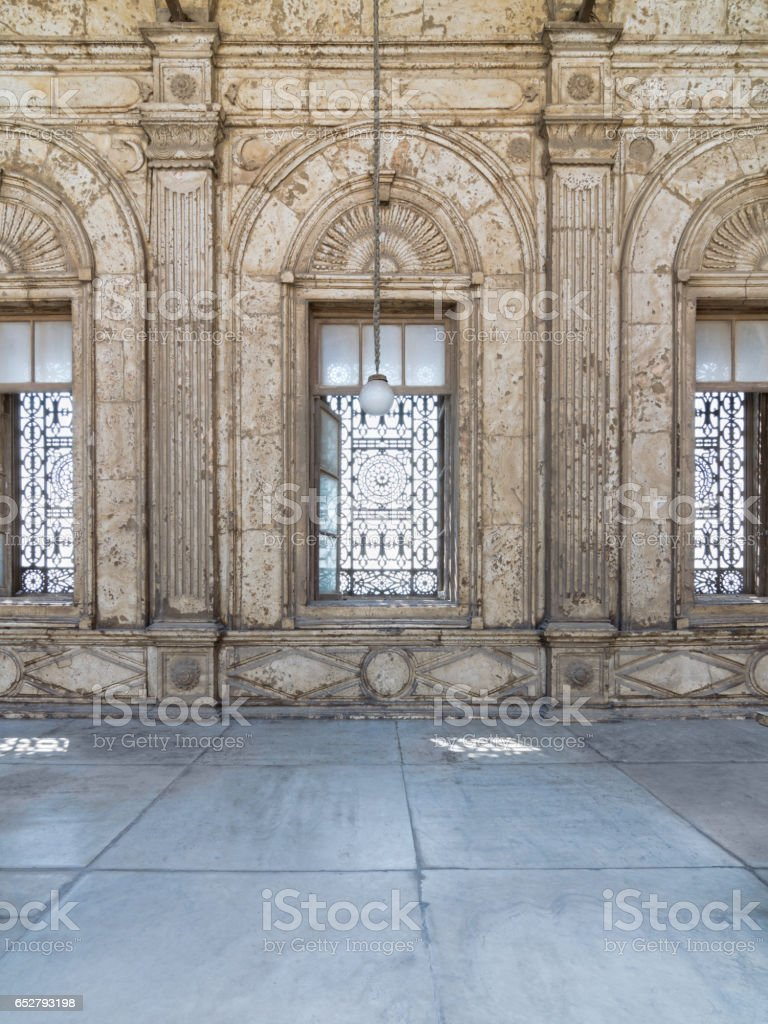Three adjacent arched windows with decorated iron grid over white marble decorated wall stock photo