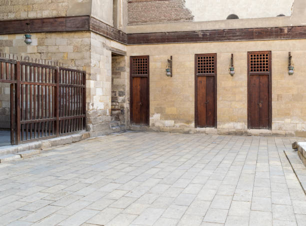 Three adjacent doors in a stone bricks wall and wooden fence, Sultan Al Nassir Qalawun Mosque stock photo