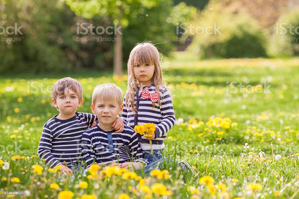 Three adorable kids, dressed in striped shirts, hugging and smil stock photo