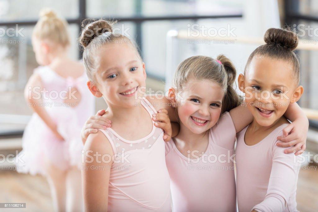Três adoráveis jovens bailarinas sorriam de braço dado - foto de acervo