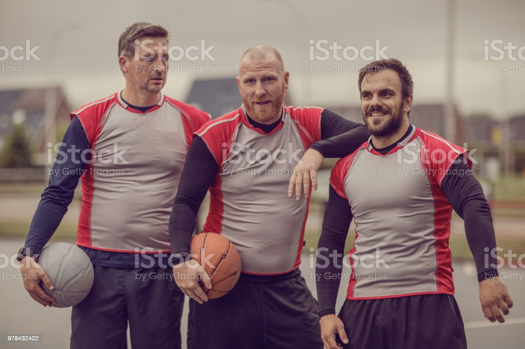 Three adult male players of a basketball team during a street ball...
