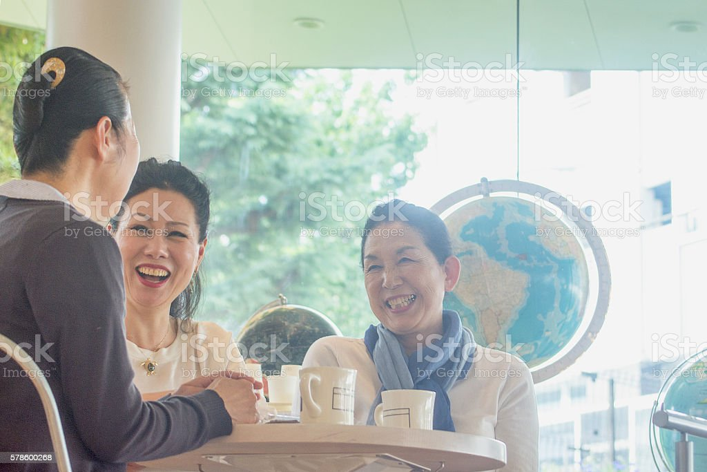 Three adult women chatting at a coffee shop stock photo