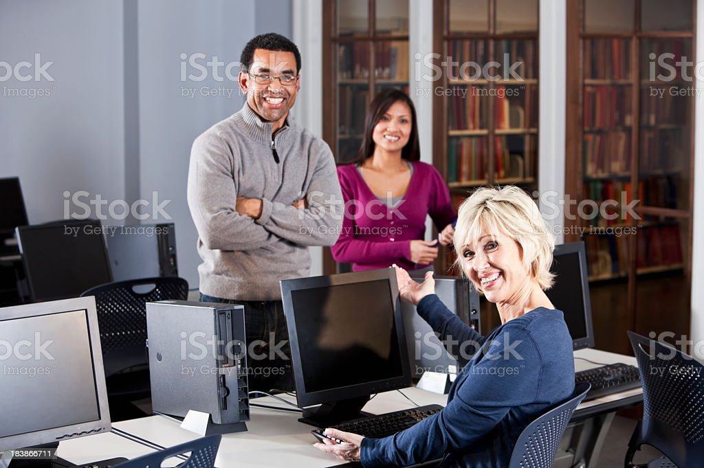Three adults in computer lab stock photo