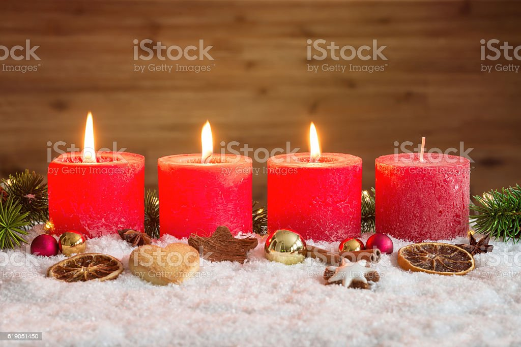 Three advent candles lit in snow stock photo