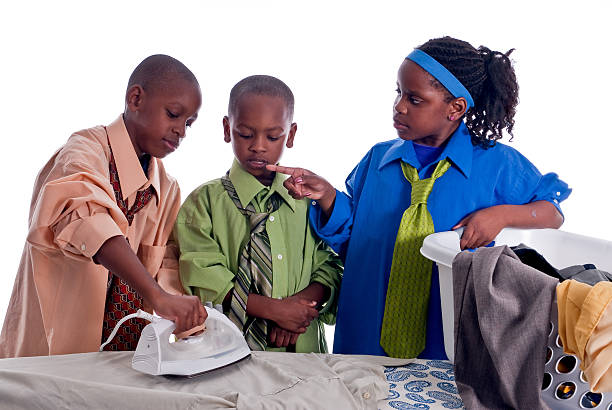 Three African American children learning how to iron stock photo
