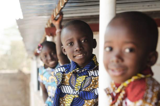 drei afrikanische kinder lächeln und lachen im freien - wohltätigkeit und humanitäre hilfe stock-fotos und bilder