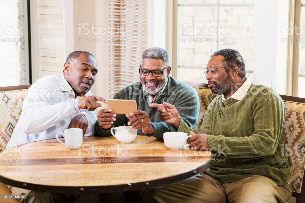 A group of three African-American men wearing sweaters and...