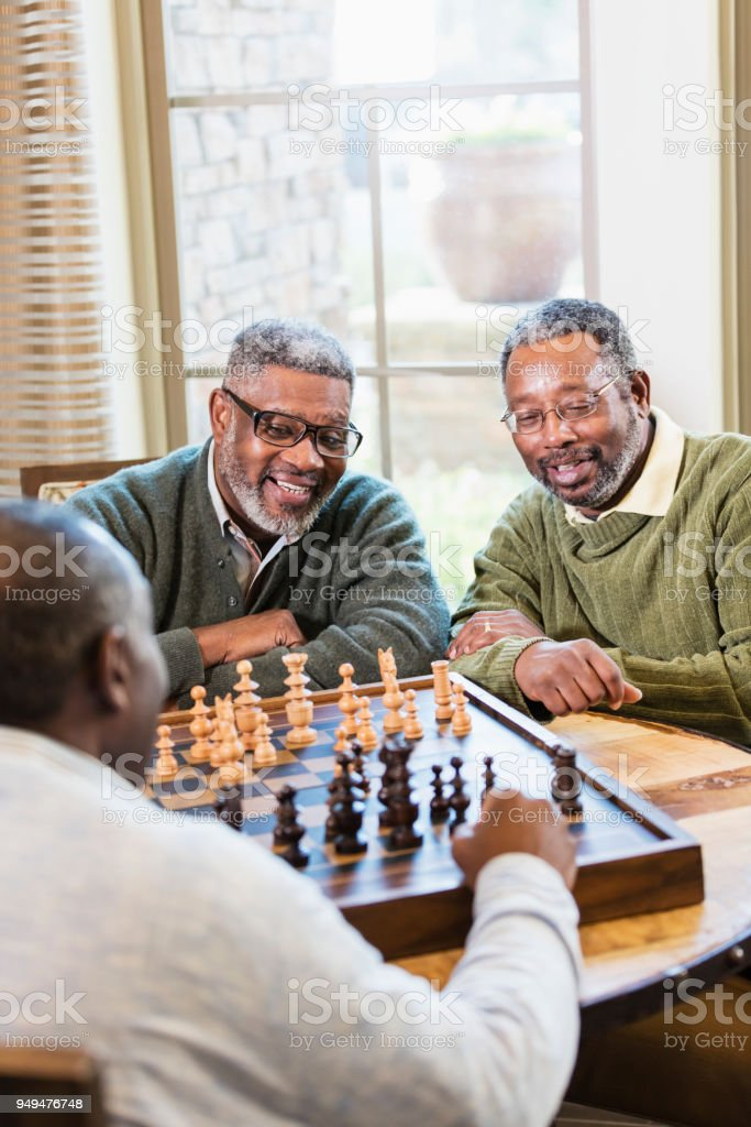 Three African-American men playing chess stock photo