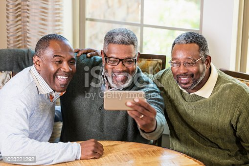 A group of three mature and senior African-American men taking a selfie together. The senior man holding the mobile phone is in his 60s. His friends are in their 50s.