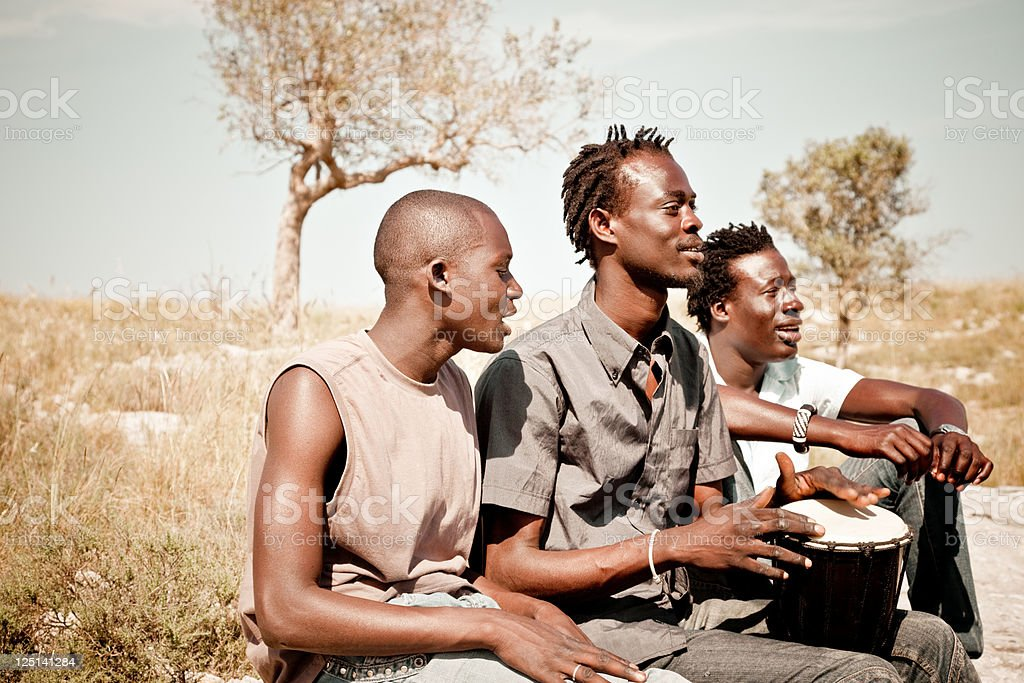 Three Africans Men Playing Djembe In The Meadow stock photo