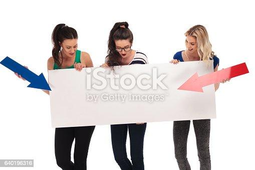 istock three amazed women pointing arrows to a big blank board 640196316