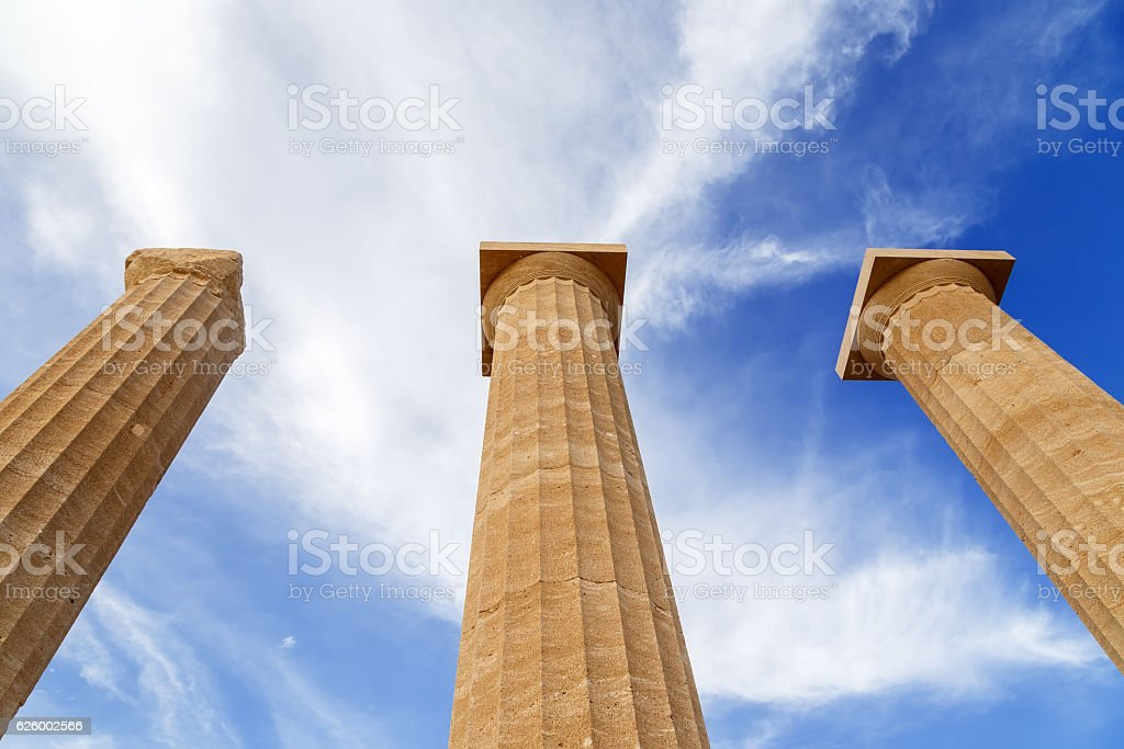 Three ancient greek pillars against blue sky stock photo