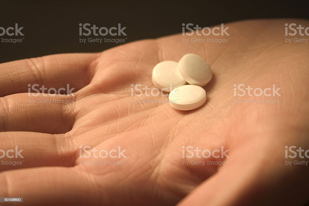 Three Antacid Tablets in a Woman's Palm - Close-Up stock photo