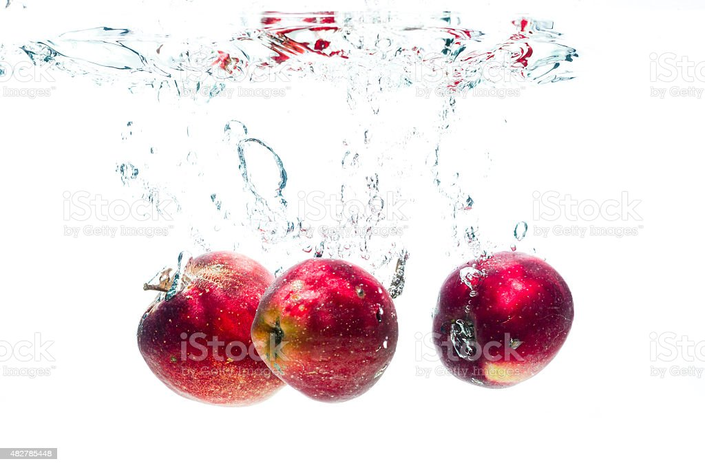 Three apples fall deeply under water stock photo