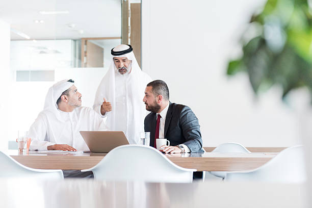 Three Arab businessmen in business meeting in modern office Business professionals using laptop, discussion, teamwork, co-operation arabia stock pictures, royalty-free photos & images