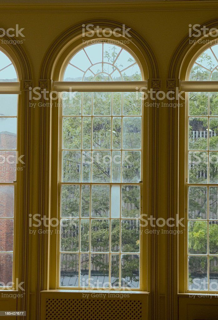 Three arched windows look out to garden royalty-free stock photo