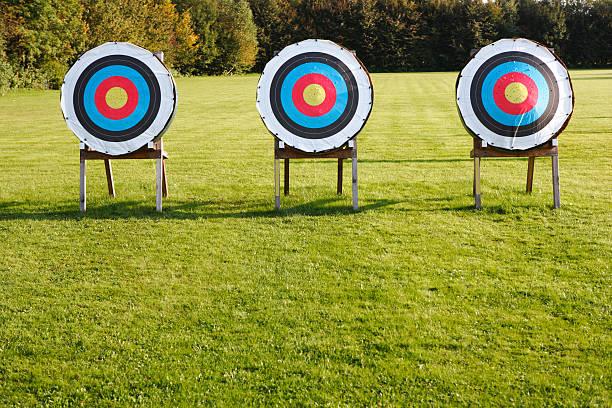 trois objectifs de tir à l'arc dans une rangée sur green meadow - tir à l'arc photos et images de collection