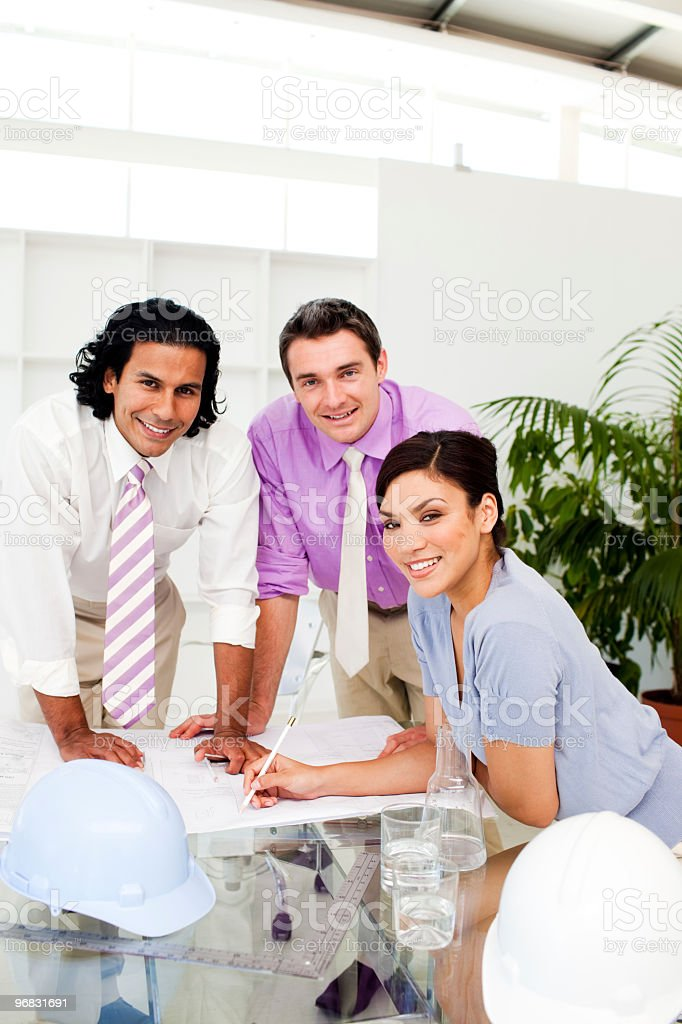 Three architect co-workers studying plans royalty-free stock photo