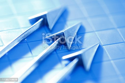 Three upwardly pointing arrows sit on top of a grid photographed with a very shallow depth of field.