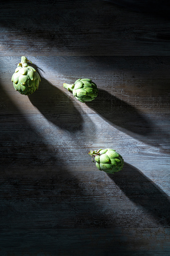 Three artichokes on gray wooden table and beam of light with moody dark surrounding.