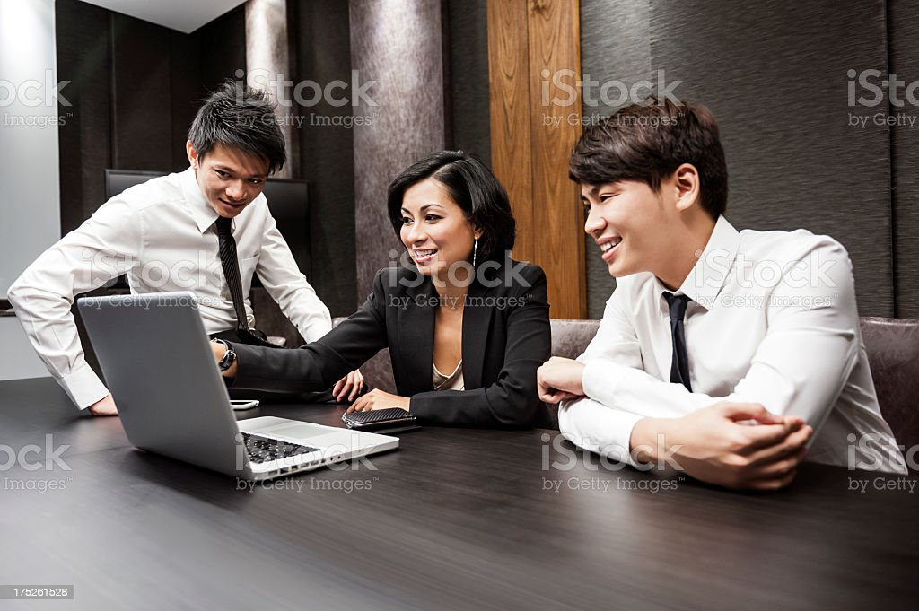 Three Asian business people sitting at a table and working royalty-free stock photo