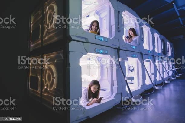 Three Asian Chinese Female Tourist Check In Capsule Hotel Room And Surfing Internet And Selfie On Their Bed With Their Mobile Phone While One Of Them Reading From Her Notebook Stock Photo - Download Image Now