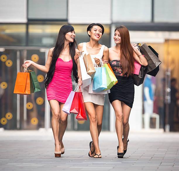 drei asiatische mädchen beim einkaufen - kleider günstig kaufen stock-fotos und bilder