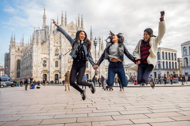 three asian women jump around the city square stock photo