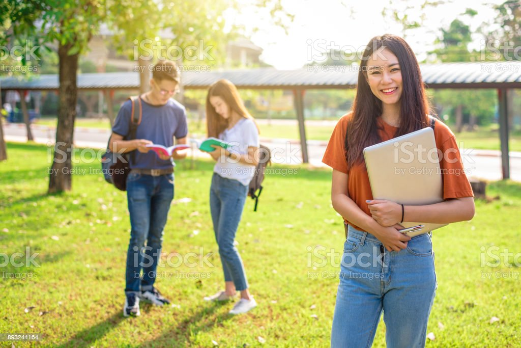 Three Asian young campus people tutoring and preparing for final examination in university. Education and learning concept. Friendship and Relation ship concept. College and Outdoors theme. stock photo