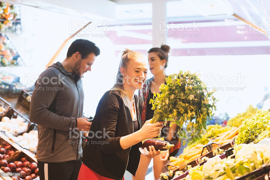 Three Athletes Having Fun While Shopping in Fruit Vegetable Market royalty-free stock photo