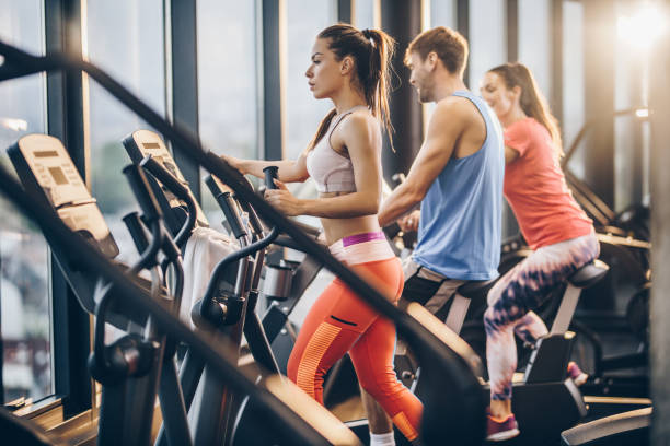 Three athletic people warming up on exercise machines in a gym. Athletic woman exercising on cross trainer in a gym while two other people are in the background. training equipment stock pictures, royalty-free photos & images