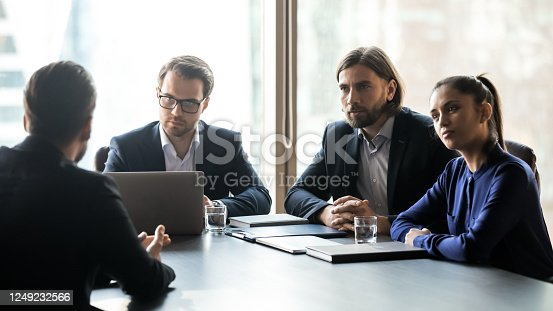 843963182 istock photo Three attentive hr managers listening to candidate on interview 1249232566