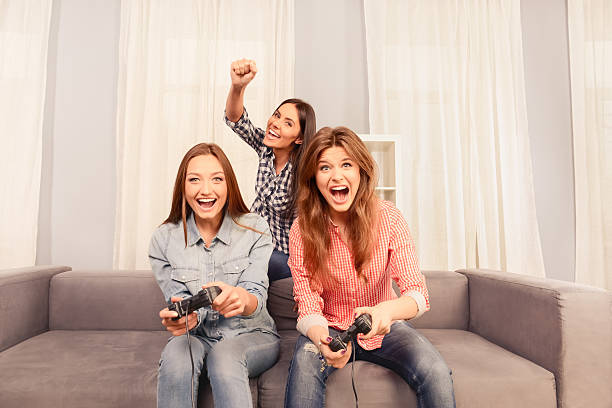 Three attractive girls sitting on sofa and playing video game - foto de stock
