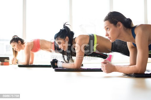 istock Three attractive sport girls doing plank exercise in fitness class. 598675758