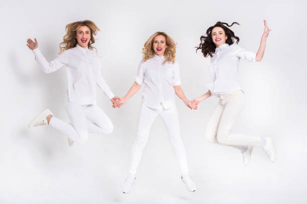 Three attractive women in white jumping on white background stock photo