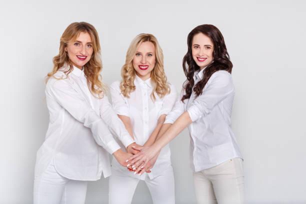 Three attractive women in white portrait on white background stock photo