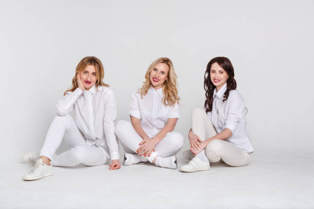 Three attractive women in white sitting on the floor on white background stock photo