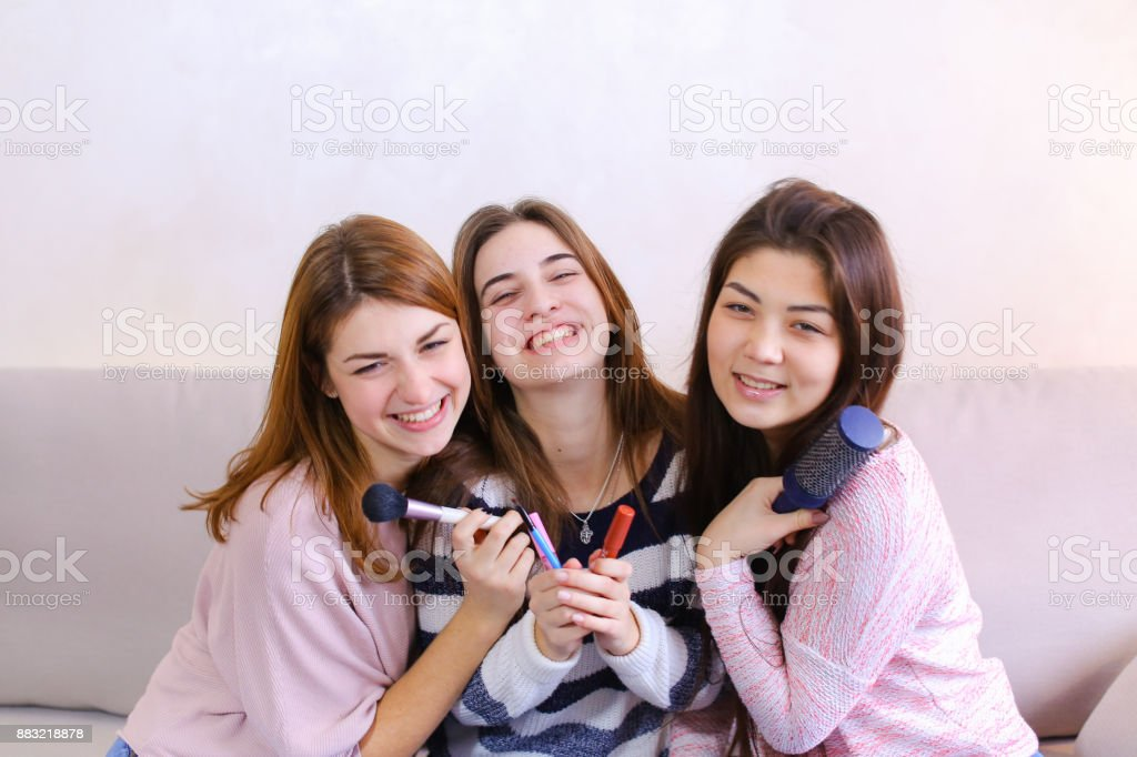 Tres atractivos jóvenes amigos posando con una sonrisa en la cámara y - foto de stock