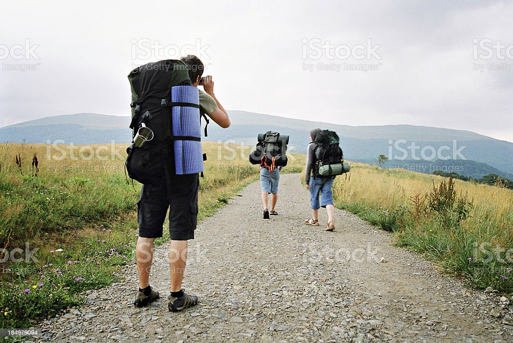 Three backpackers on a road with one of them taking pictures royalty-free stock photo