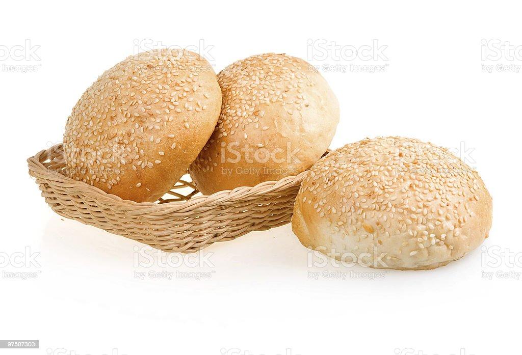 Three Baked Buns with Sesame in Basket royaltyfri bildbanksbilder